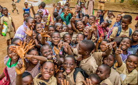 Group of Ivory kids smiling and waving